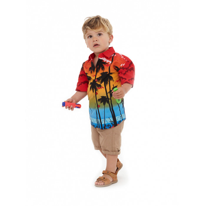 Toddler in a collared shirt that depicts a sunset against palm tree silhouettes