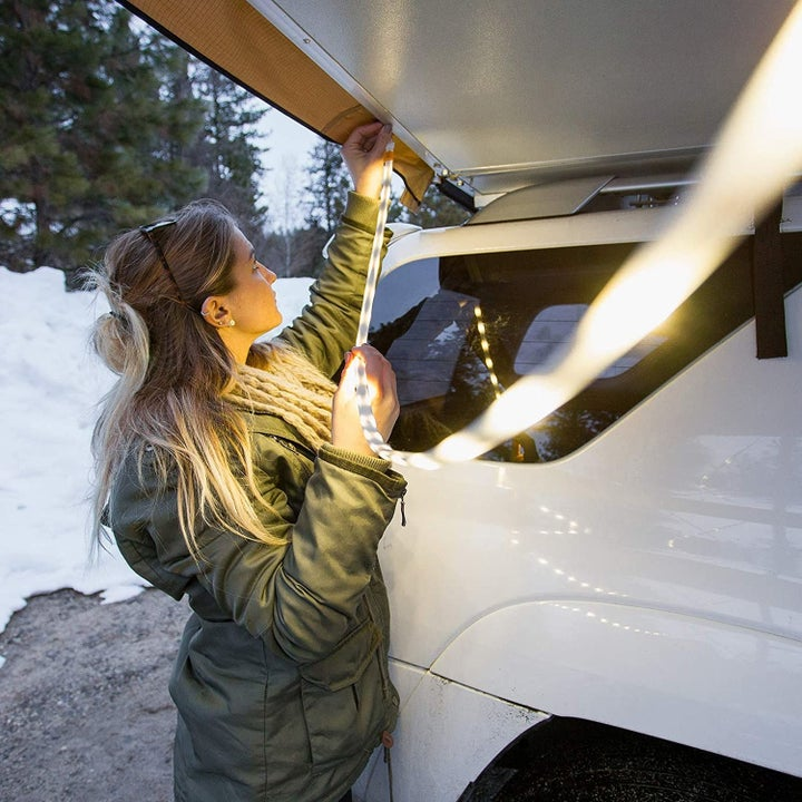 Woman attaching luminoodle to the covering above her car