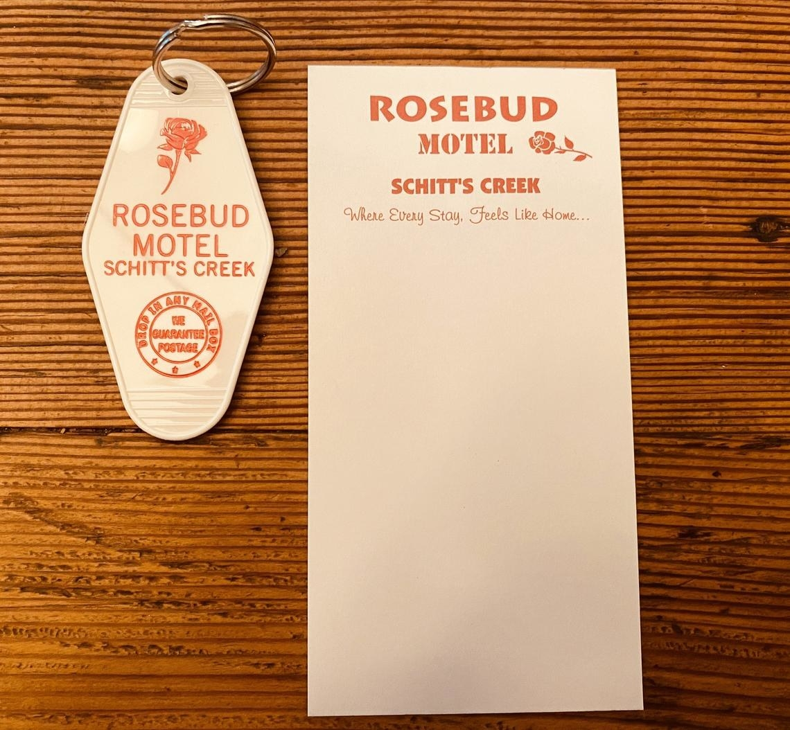 white motel keychain that says rosebud motel and a matching long notepad