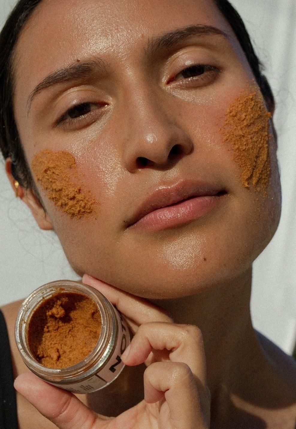 Model applies Noto Botanics' Resurface Scrub on their face