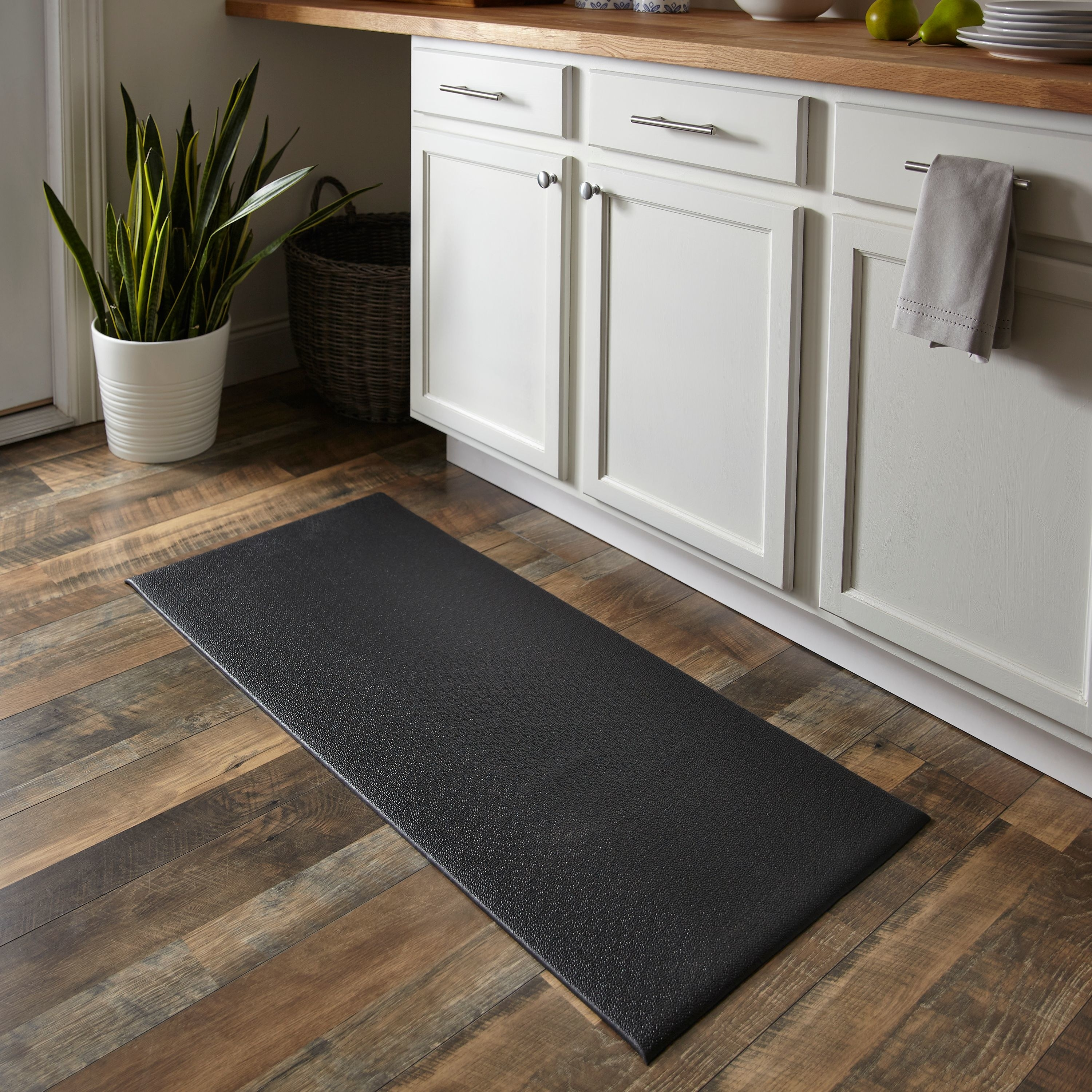 Black kitchen mat on a wooden floor, in front of white cabinets