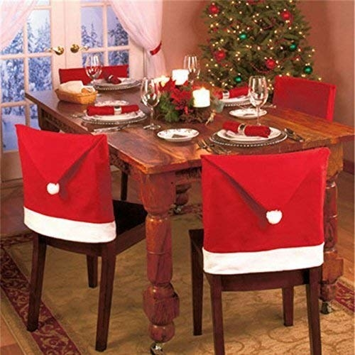 Chairs around a decorated Christmas dinner table adorned with chair covers that resemble a Santa hat.