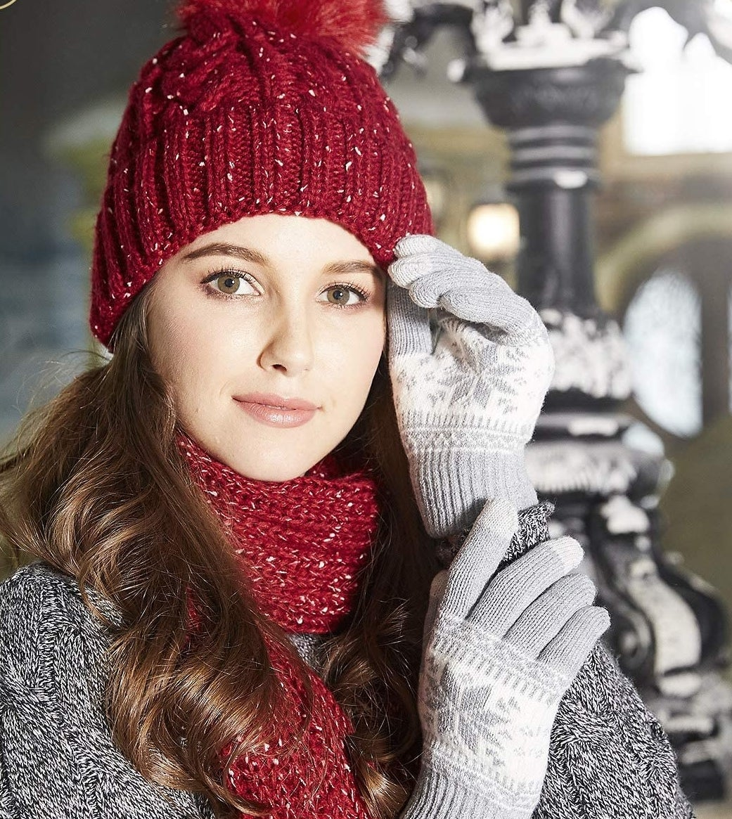 A person wearing a knit hat, scarf, and gloves