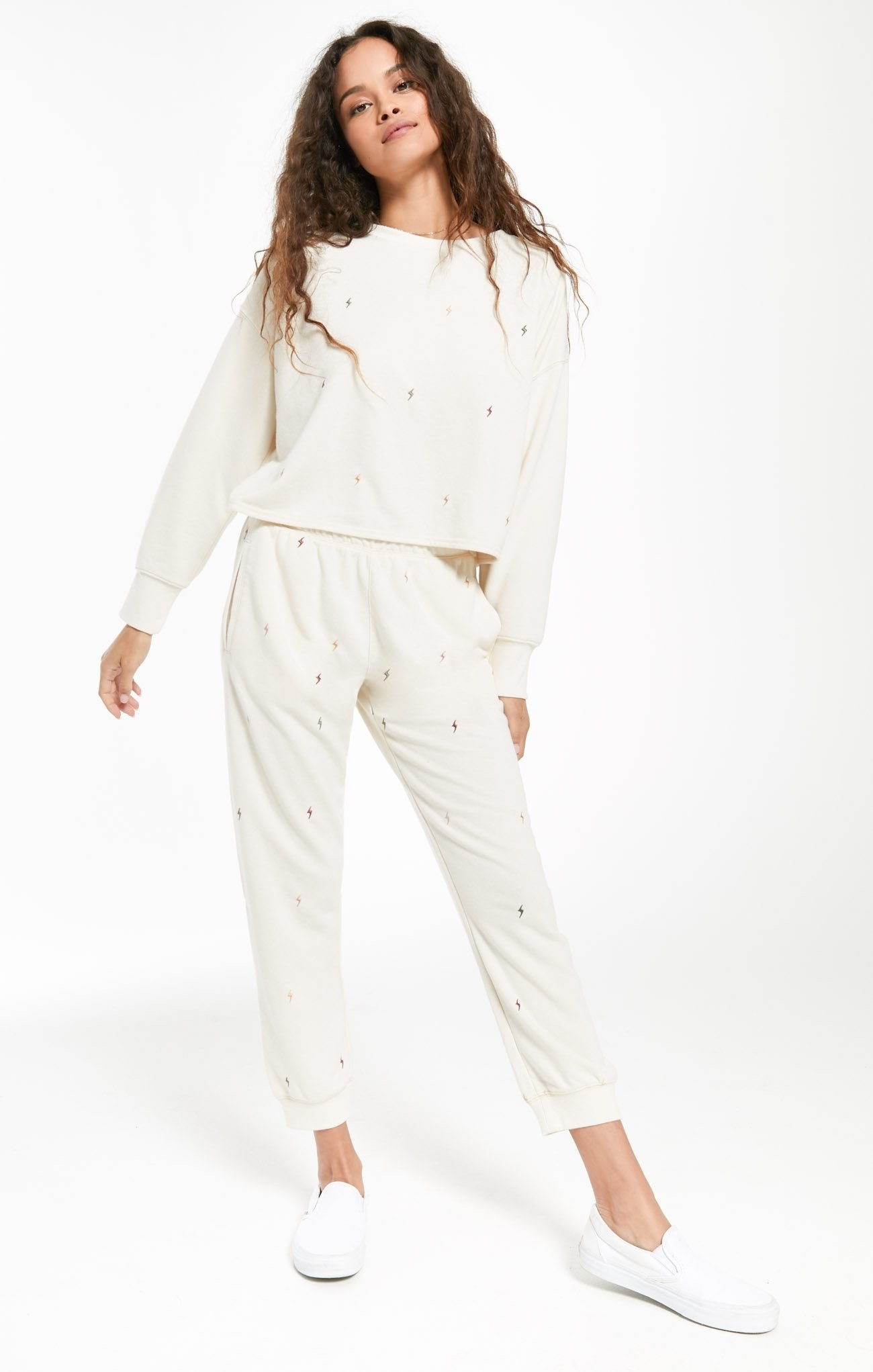 a model wearing a white sweatshirt and pants with tiny gold lightning bolts on it
