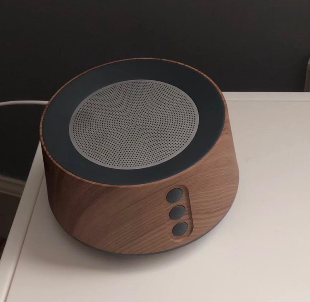 reviewer photo showing white noise machine on their nightstand