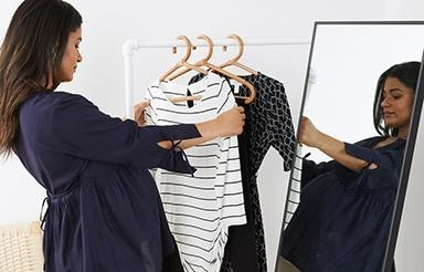 pregnant model looking at maternity items on a clothing rack
