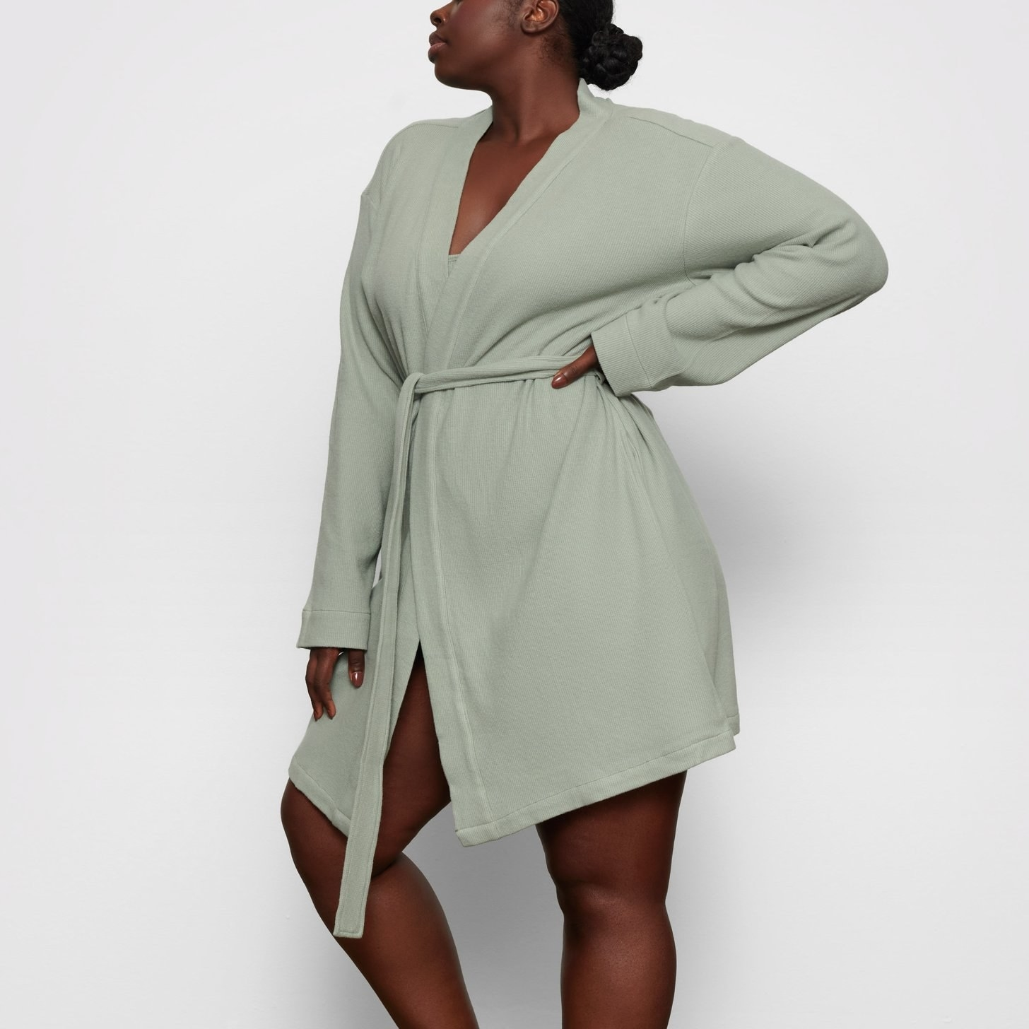a model in the short robe in light sage green