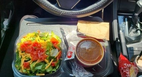 Reviewer eating a meal in their car with the lap desk