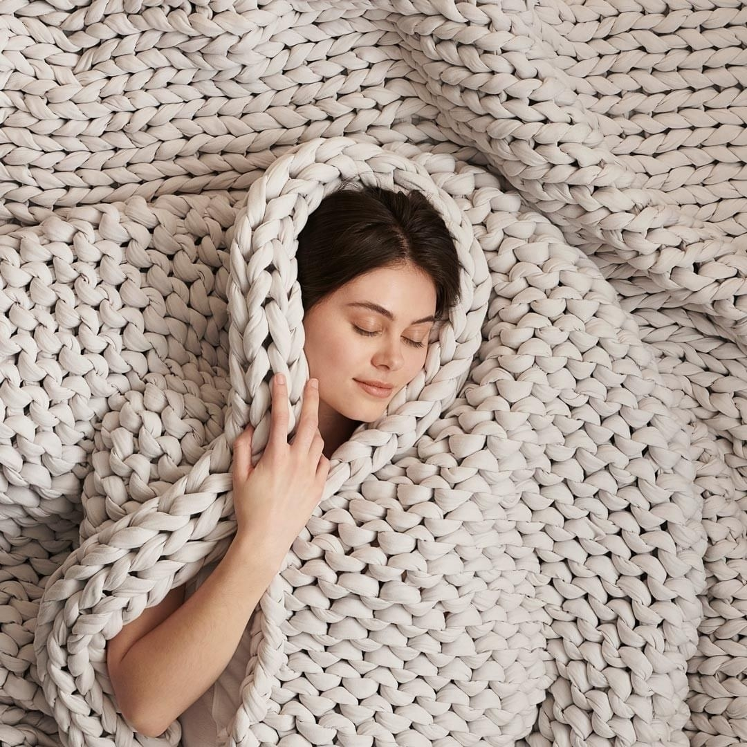 a model cuddled up in an ivory knit weighted blanket