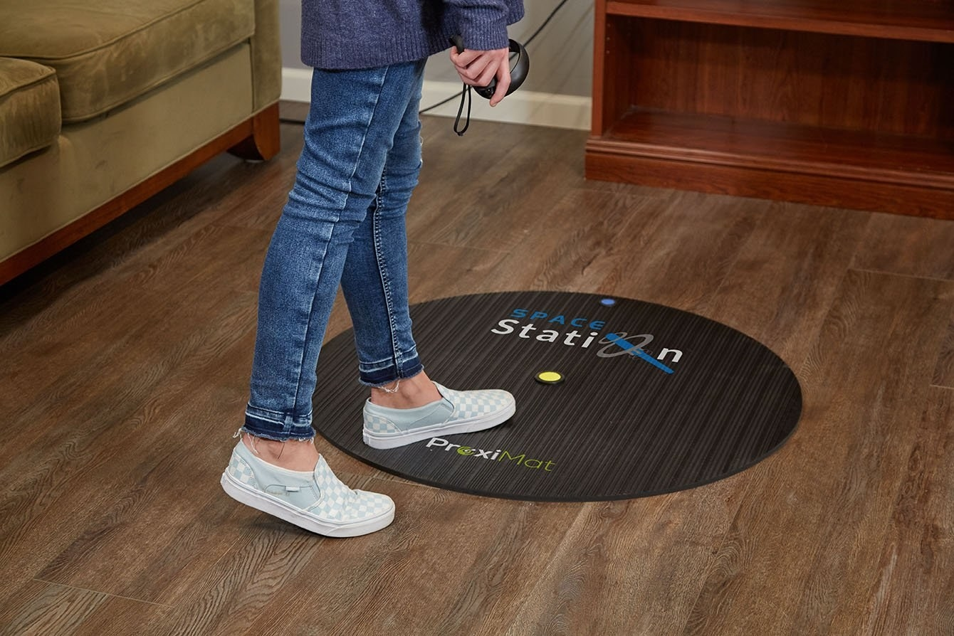 Model standing on the circle mat, which has a raised button in the center in the front