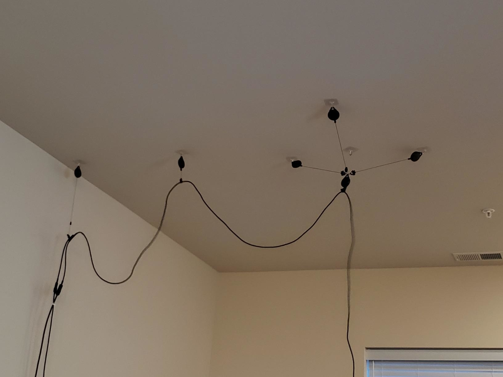 Reviewer photo of their cables attached to pulleys on the ceiling