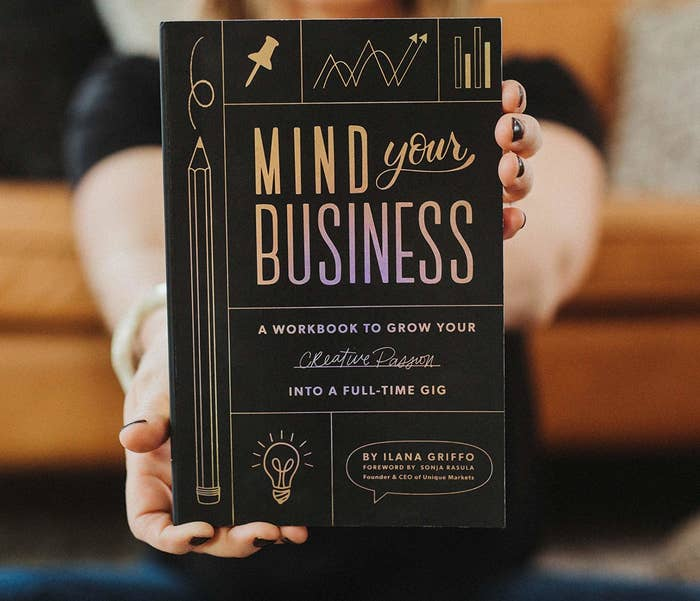 a person holding a copy of the book mind your business a workbook to grow your creative passion into a full-time gig