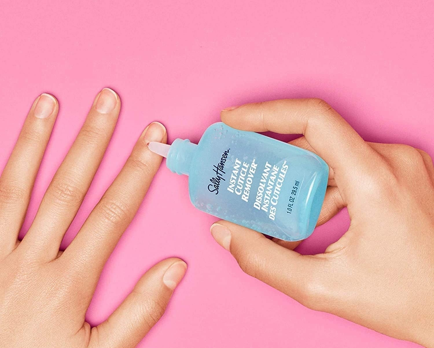A person holding the cuticle removing solution to their cuticle