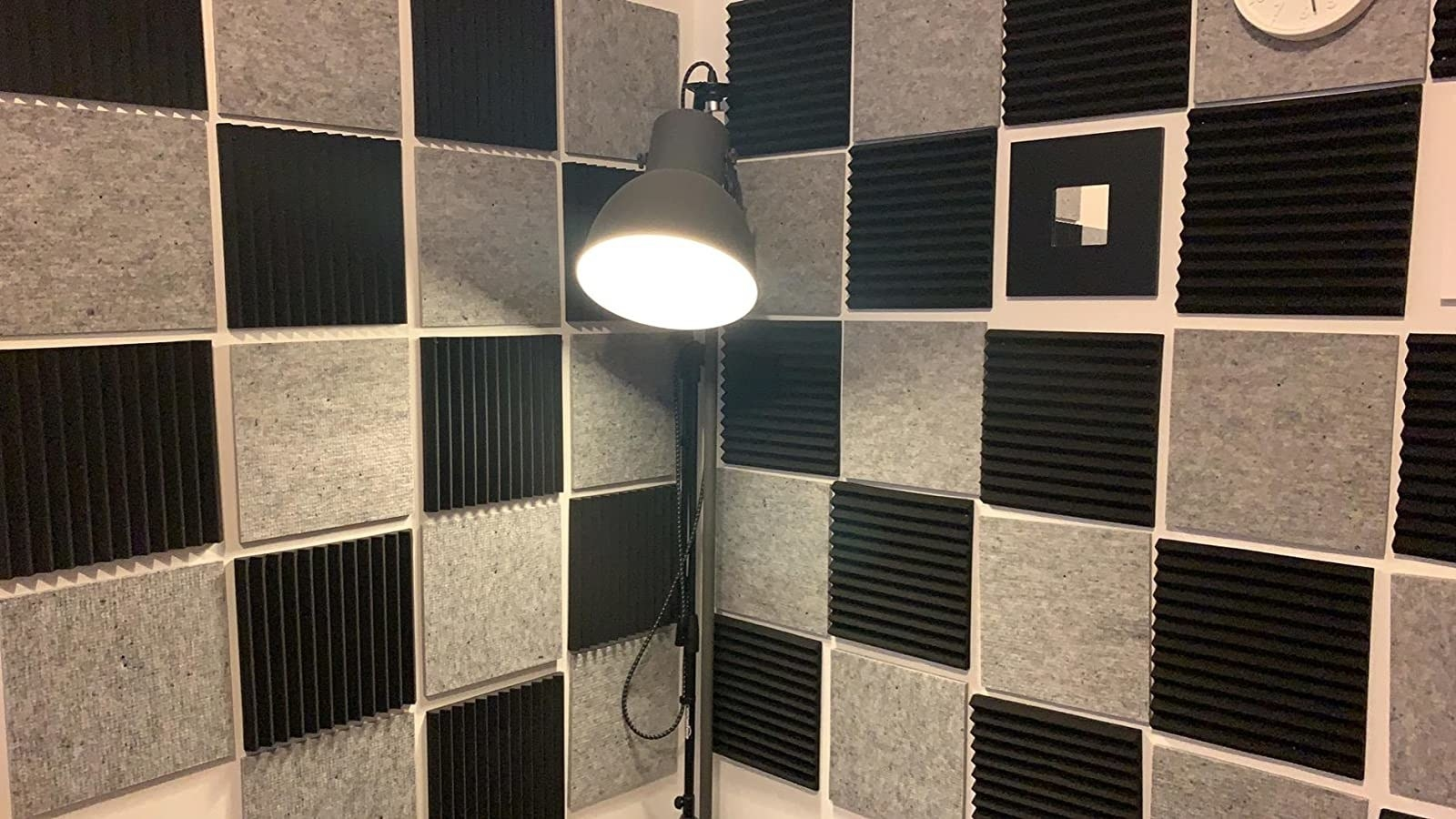 reviewer photo showing the panels in two colors arranged in a checkered pattern on their wall in their at-home recording studio