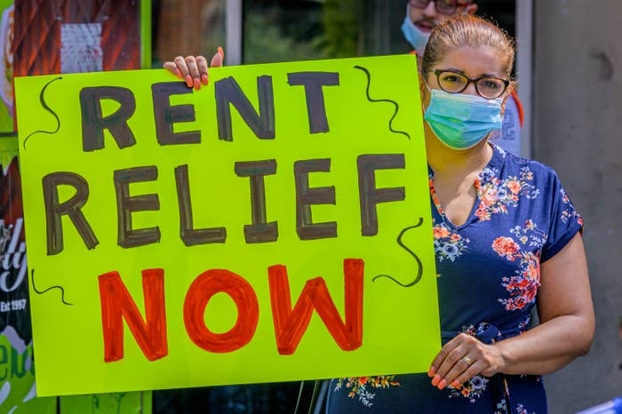 "A woman with a sign that says ""Rent relief now"""