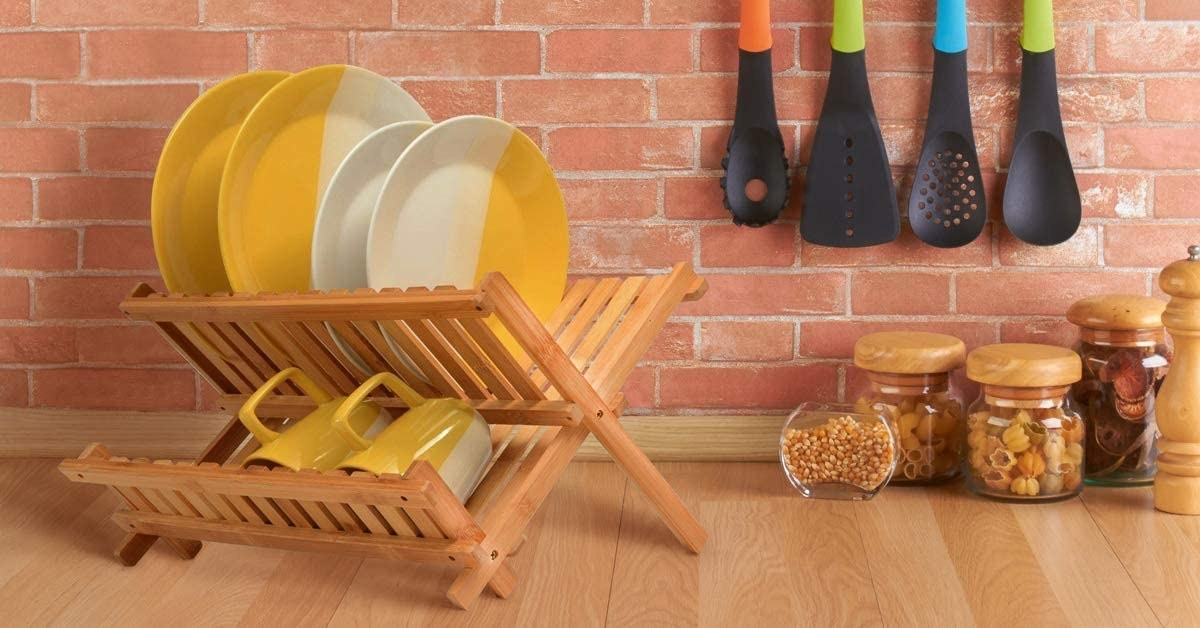 A drying rack with two shelves for plates and mugs on a counter next to some pantry jars and cooking utensils