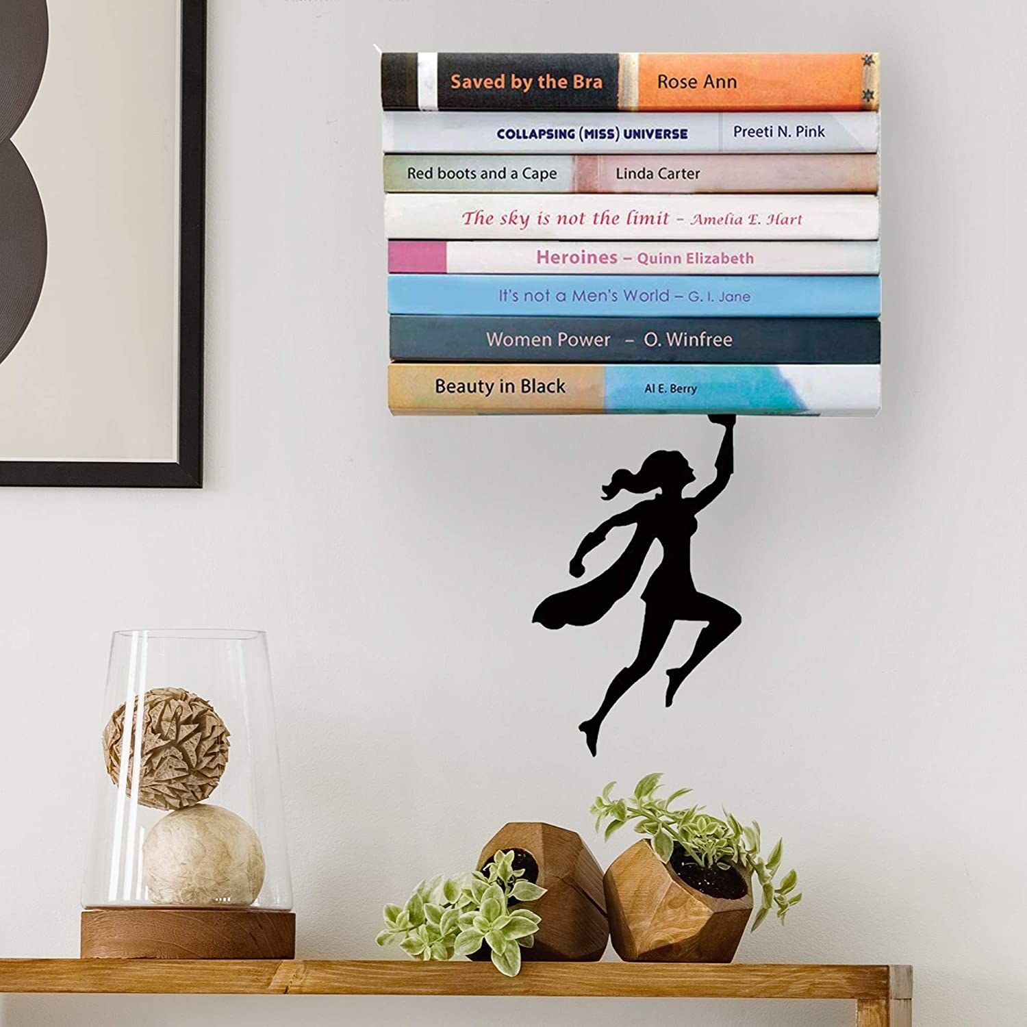 A superhero holding up a pile of books above a desk with decor and plants on it