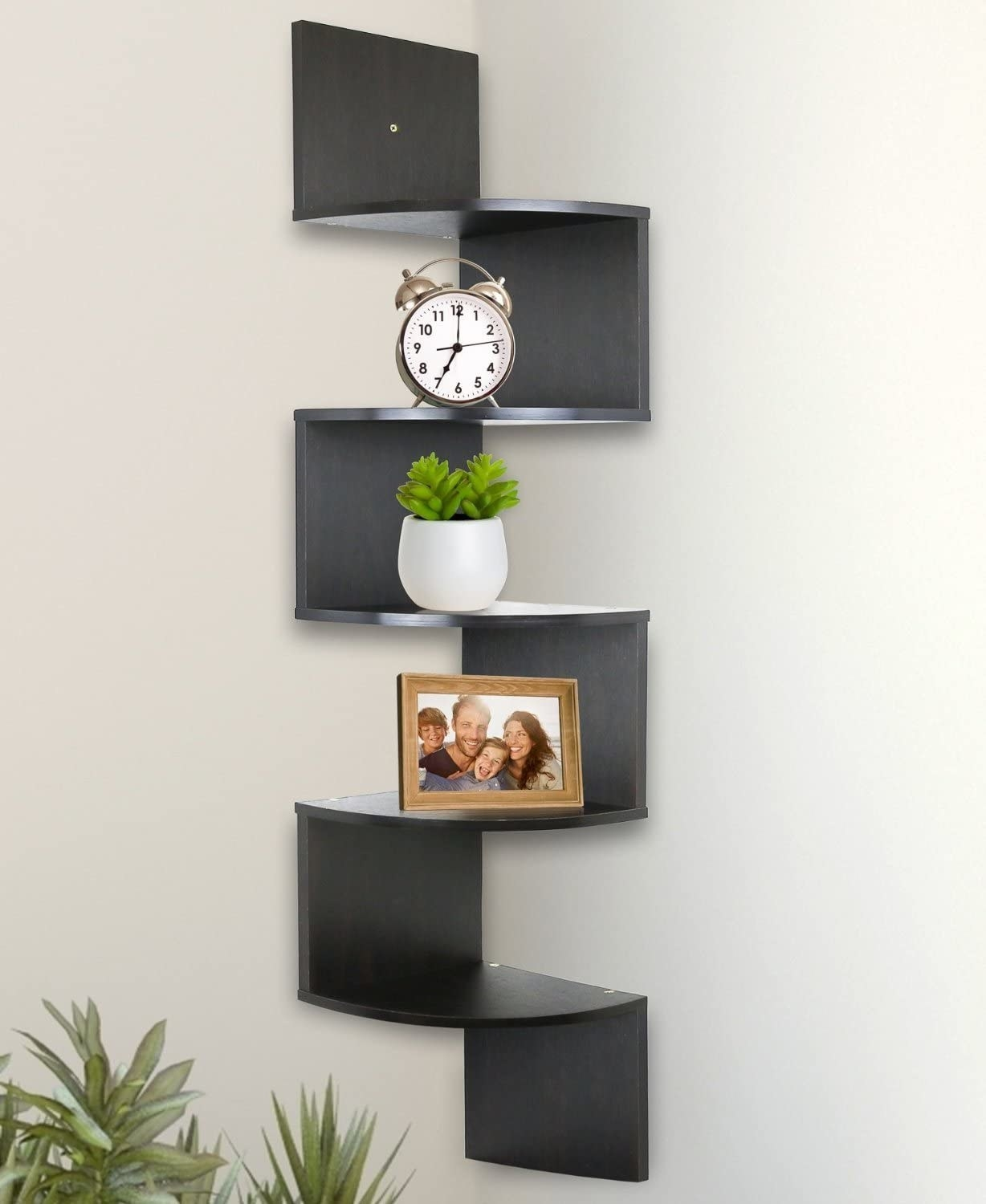 A corner shelf with a clock, plant, and picture frame on it