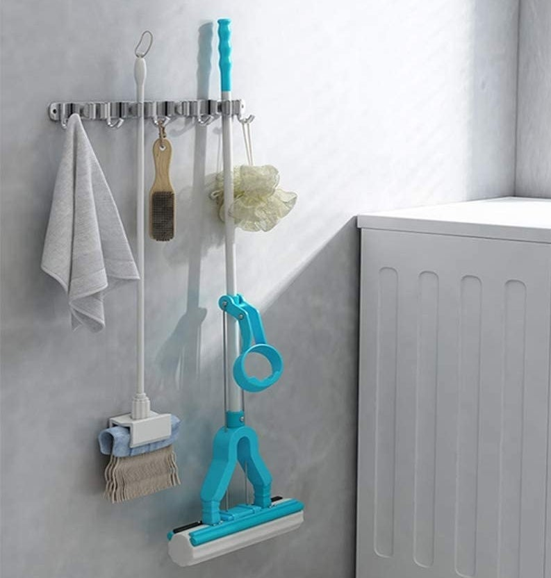 A towel, broom, brush, mop, and sponge hanging off the rack next to a washing machine