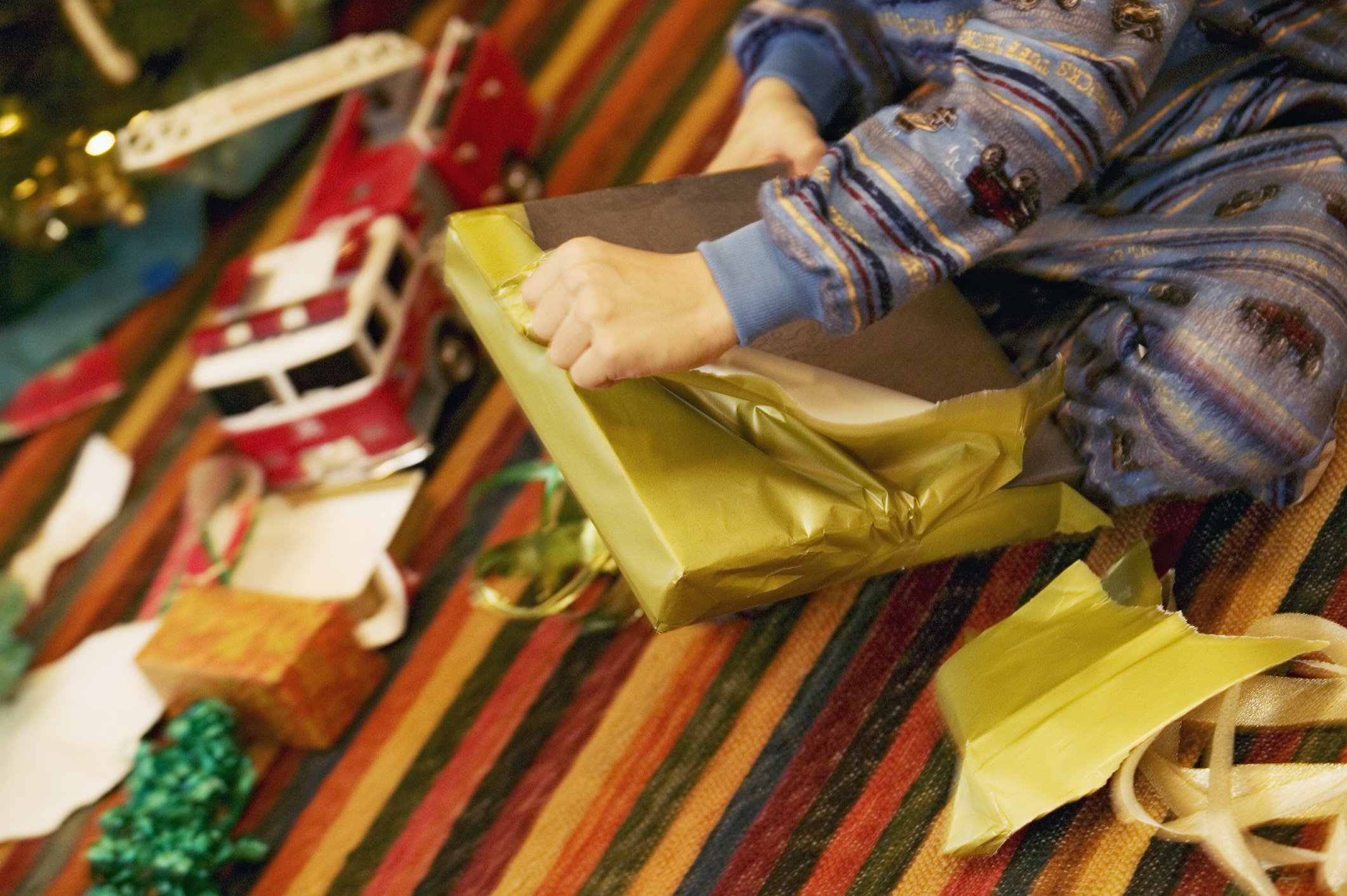 A close-up photo of a kid sitting on the floor opening a Christmas gift