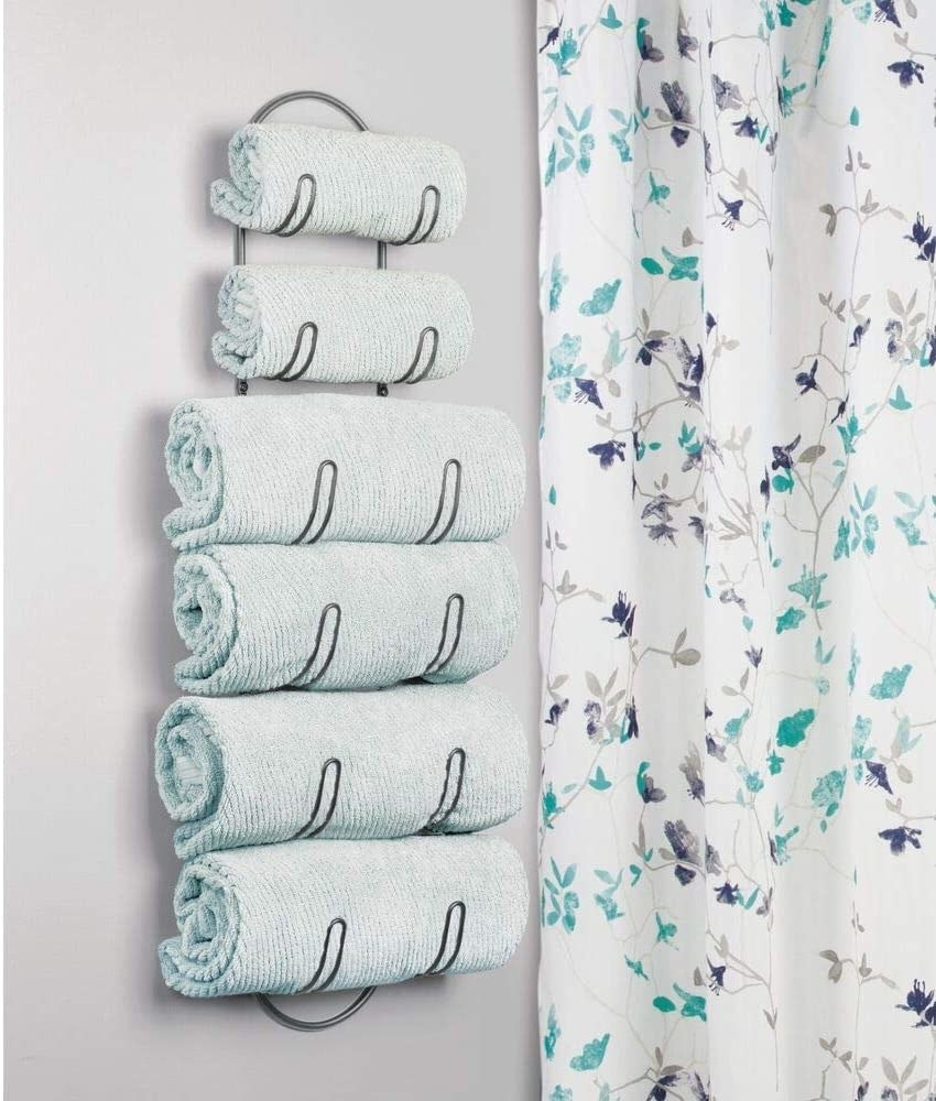 The towel rack holding four large towels and two hand towels