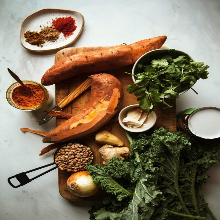Sweet potatoes, lentils, kale, onions, and ginger on a cutting board.