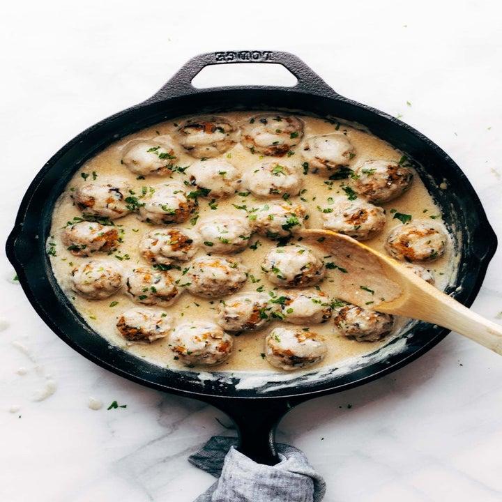 Mushroom meatballs in a skillet simmering in gravy.