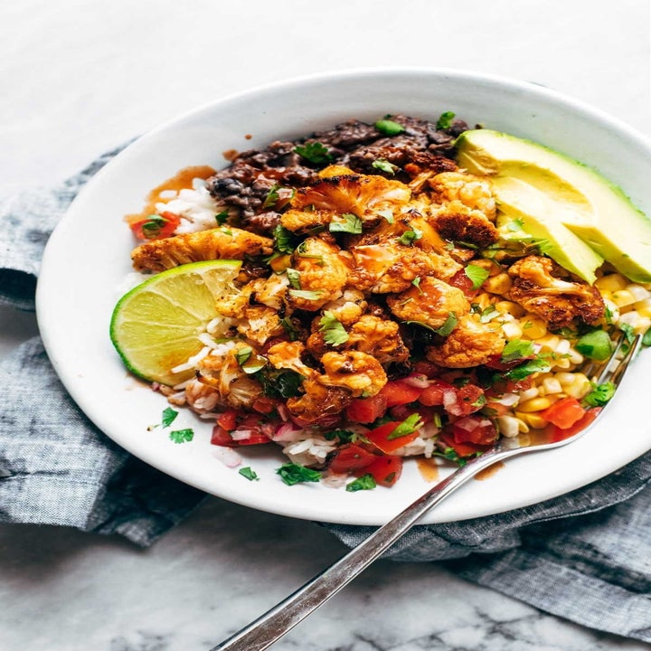 Roasted cauliflower burrito bowls with black beans, pico de gallo, avocado, and rice.
