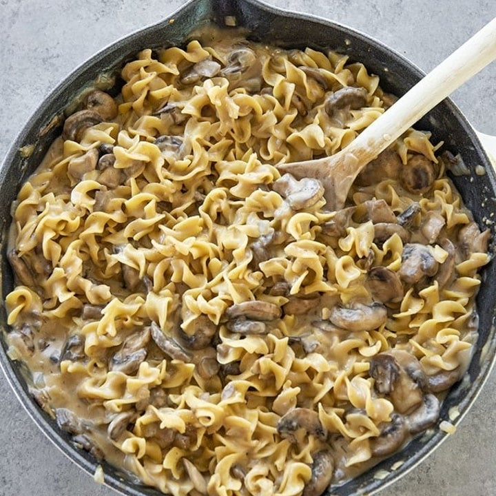 A skillet of egg noodles and mushrooms in cream sauce.