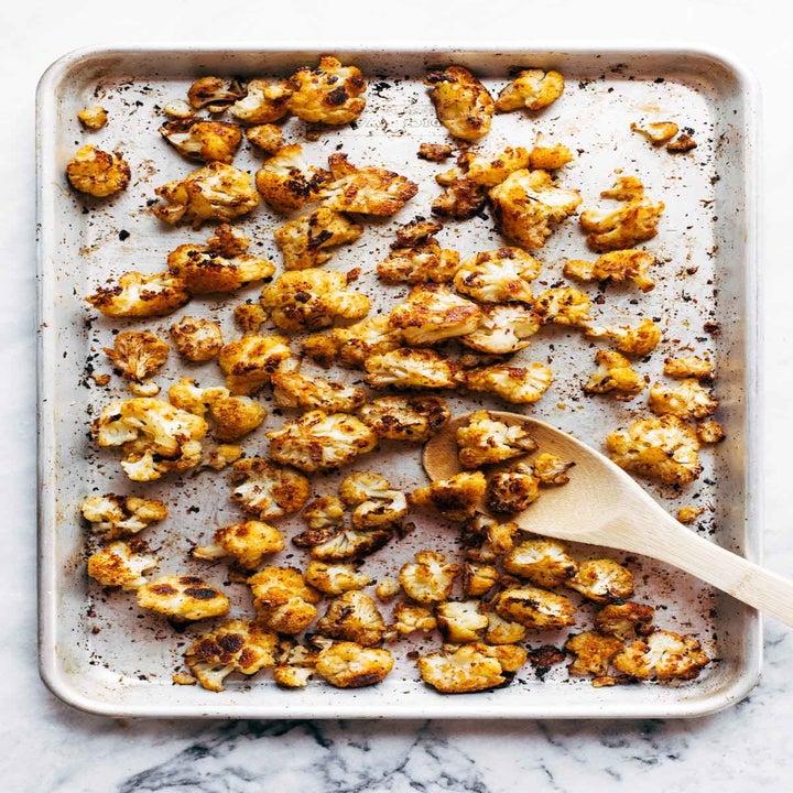 Roasted cauliflower florets on a baking sheet.