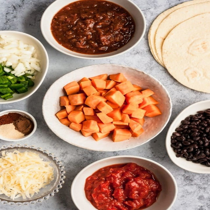 Ingredients for black bean and sweet potato enchilada casserole in small bowls.