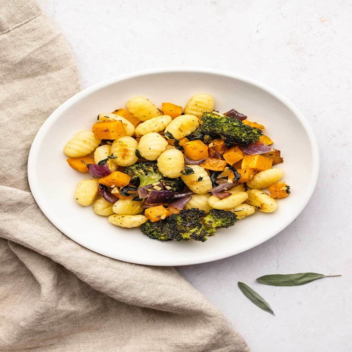 A plate of potato gnocchi with roasted veggies.