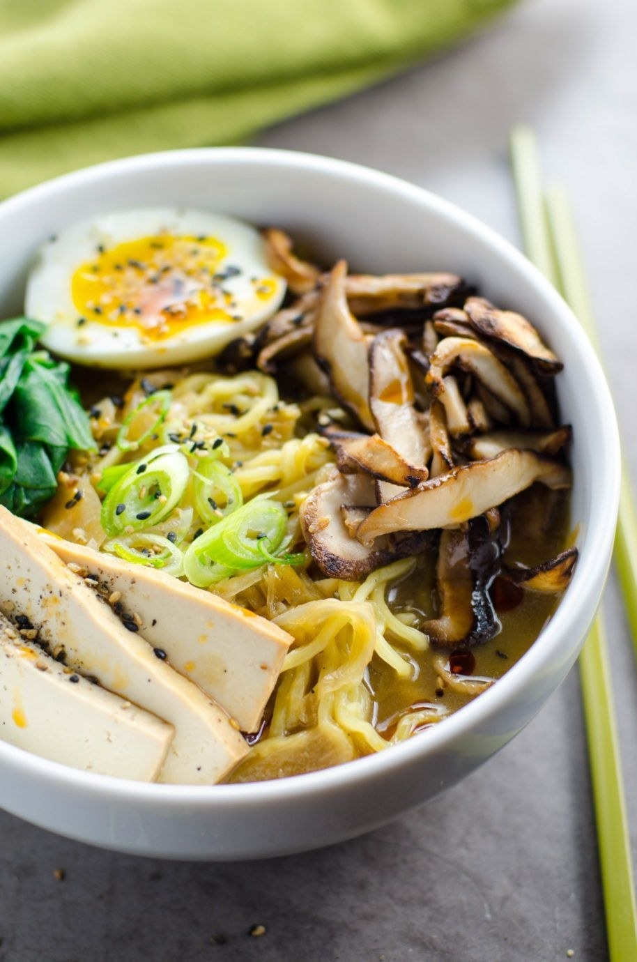 A bowl of vegetarian ramen with sliced tofu, mushrooms, scallions, and a soft boiled egg.