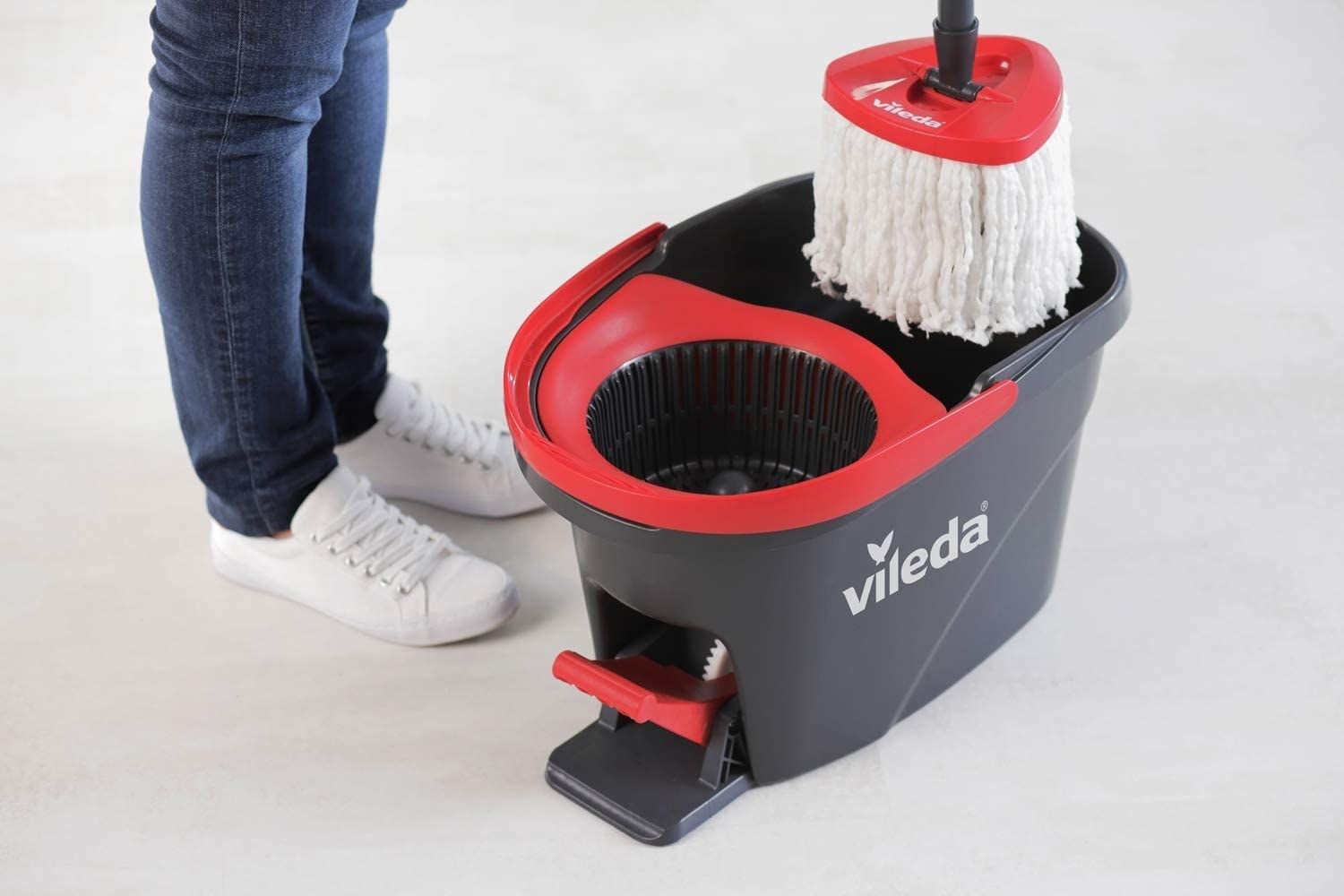 person putting the mop into the bucket