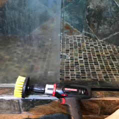 Reviewer's glass shower doors. One opaque with hard water stains and the other completely clear after being cleaned with the drill brushes