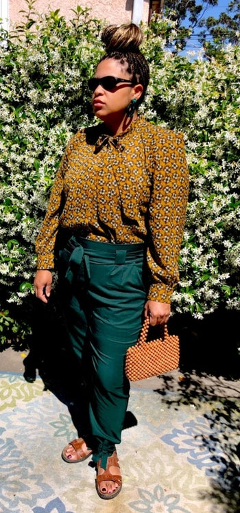 A reviewer wearing the pants in dark green