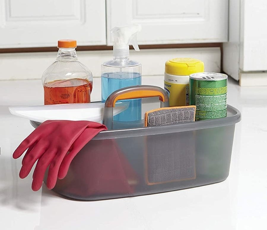 bottles of cleaning products and a sponge and glove in the caddy