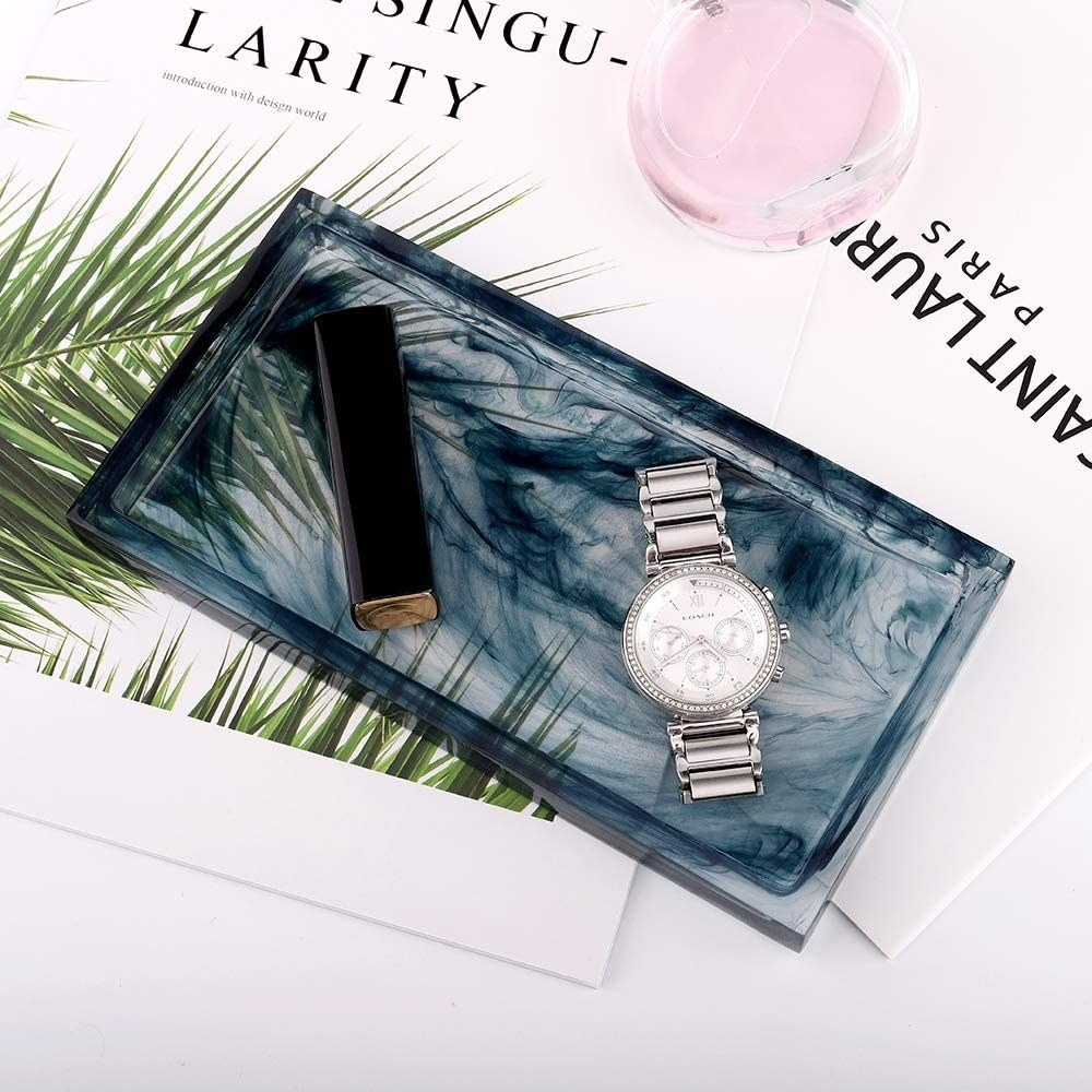 A rectangular tray with a watch and tube of lipstick on it
