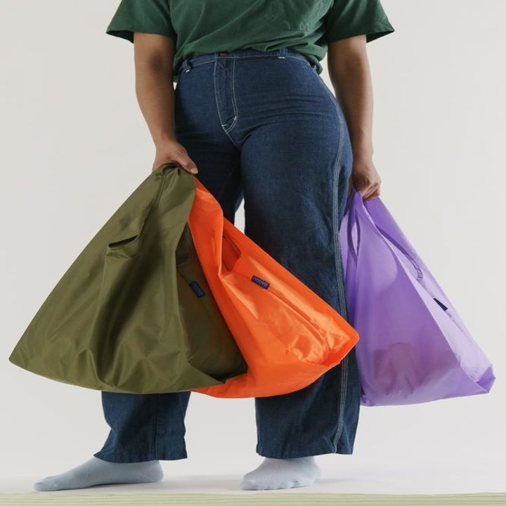 A model holding three different-colored tote bags
