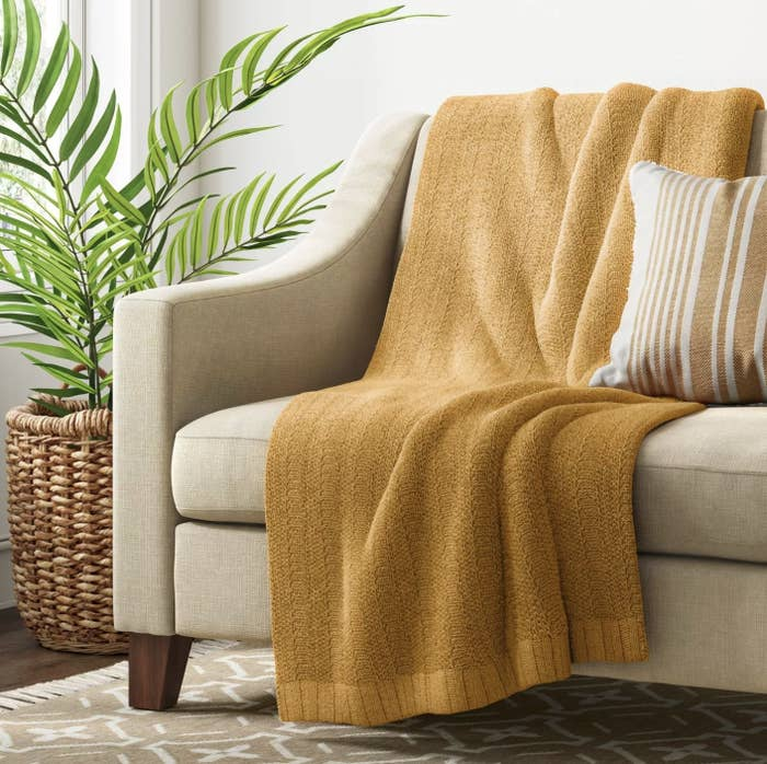 The mustard yellow throw blanket on a couch
