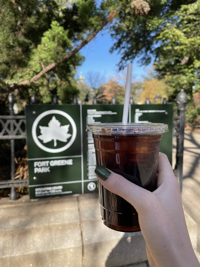Dariya holding an iced coffee while in a public park
