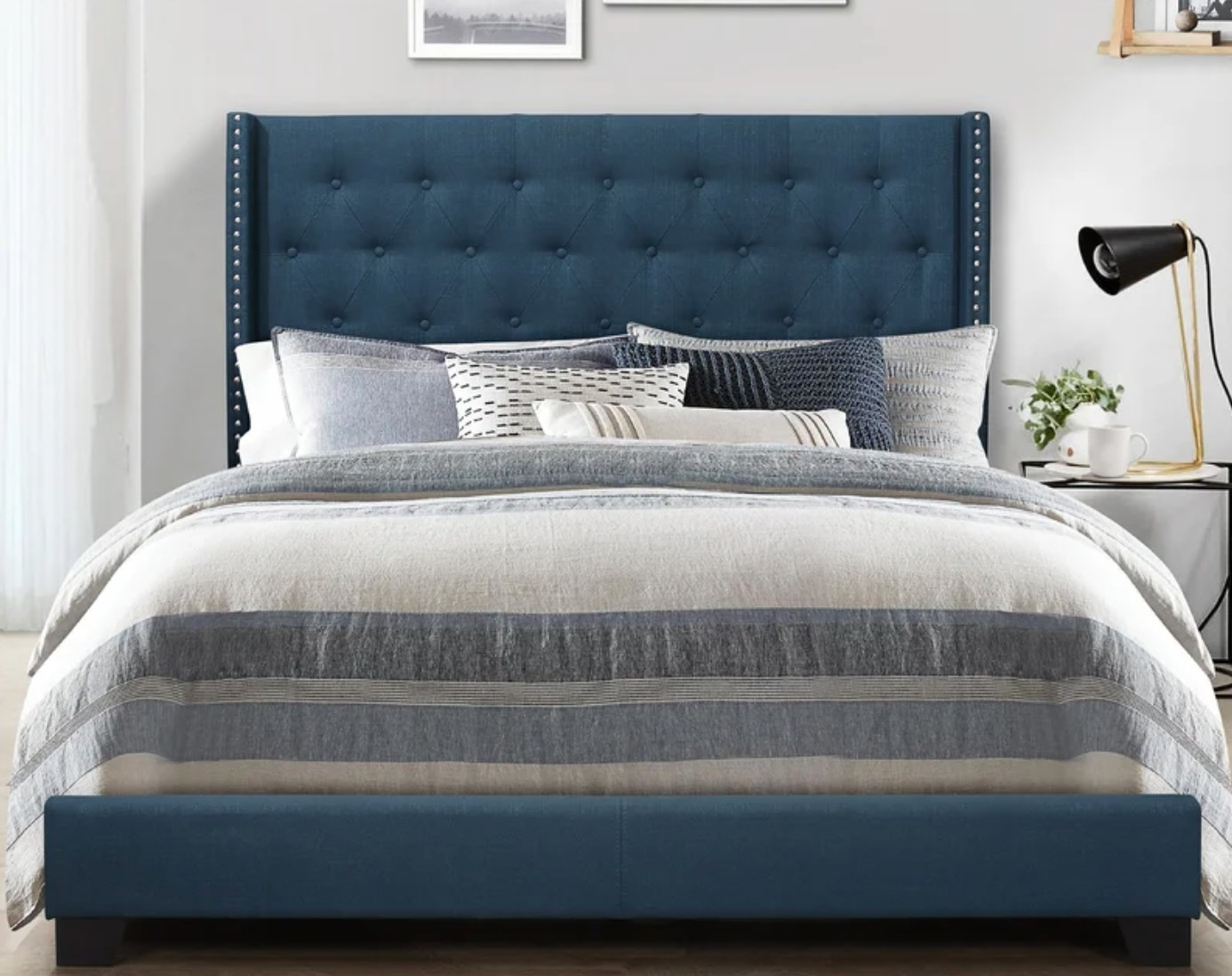 The upholstered bed frame in blue