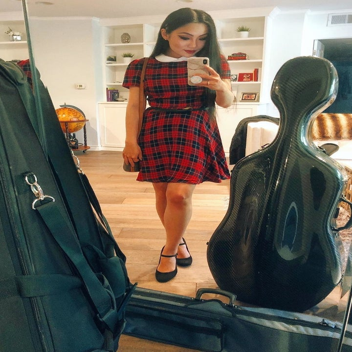 A reviewer wearing the above the knee dress in red plaid