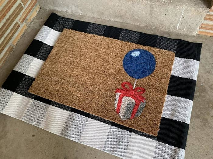 doormat with present held up with a balloon