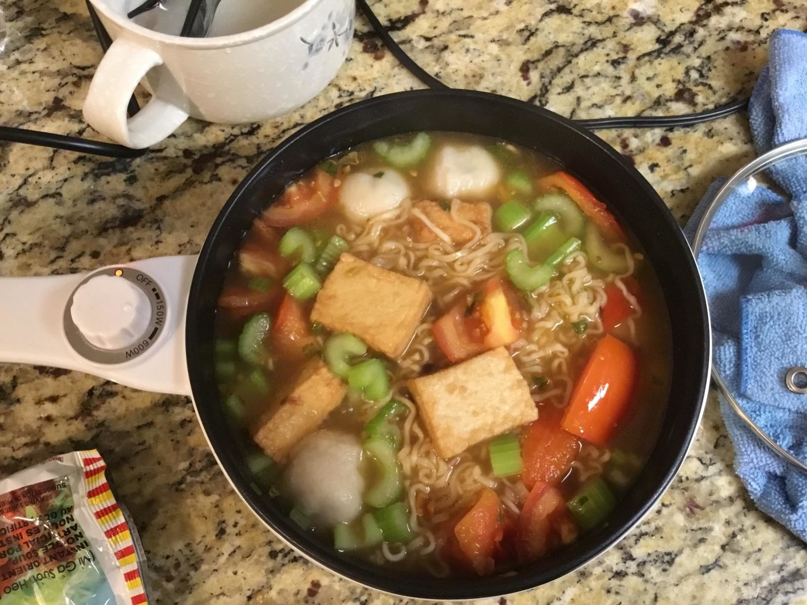Reviewer's white electric hot pot filled with ramen noodles, veggies, and tofu