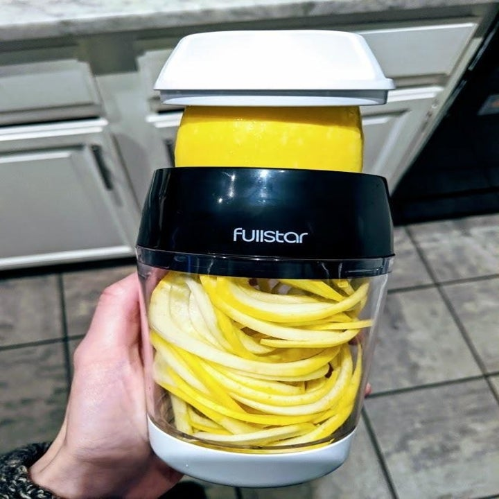 Reviewer holds veggie spiralizer with squash noodles inside