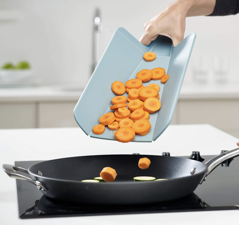 Foldable cutting board transporting veggies to pan