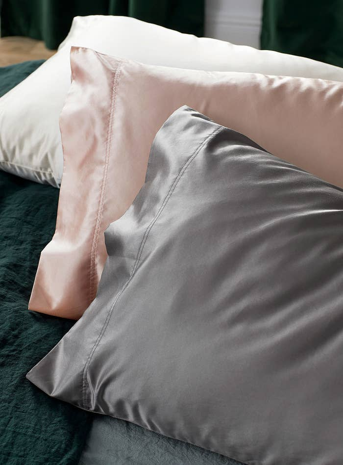 Three silky pillows on a bed