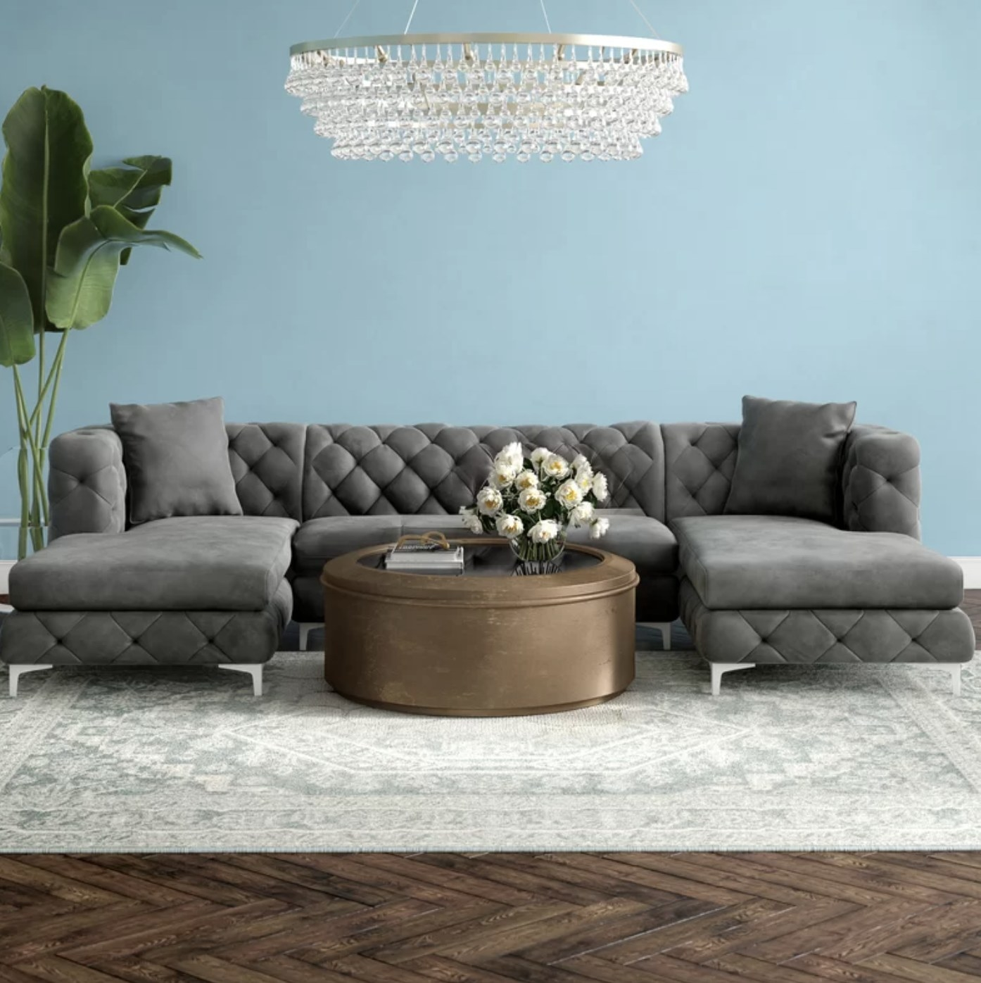the couch in grey shown in a room with a coffee table and chandelier
