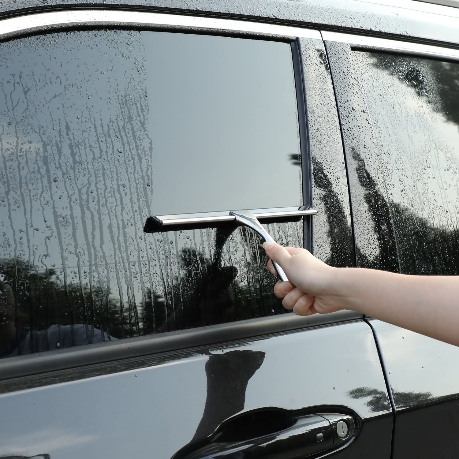person squeegeeing a car window